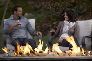 Couple Sitting by Fire Pit Drinking Wine